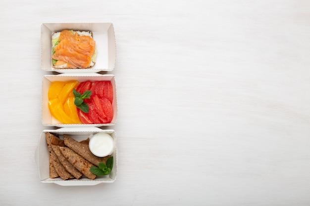白いテーブルのお弁当には、3種類のスナックサンドイッチとパンケーキとグレープフルーツ入りオレンジが入っています。健康的な食事の概念。スペースをコピーします。