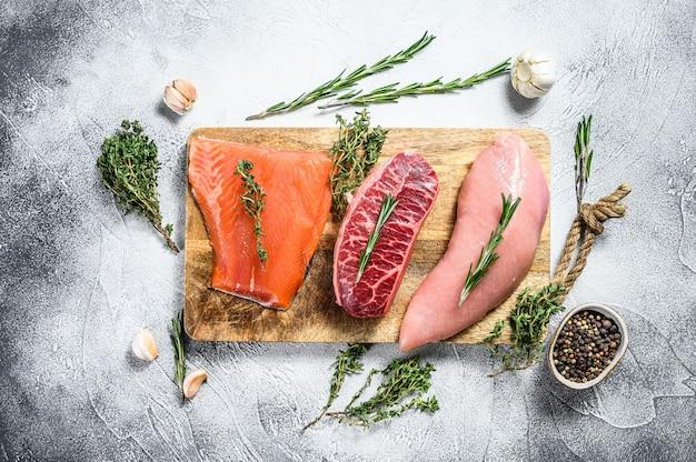 3種類のステーキ。ビーフトップブレード、サーモンフィレ、ターキーブレスト。有機魚、鶏肉、牛肉。灰色の背景。上面図。