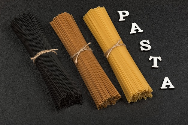 Three types of spaghetti on gray background and word pasta