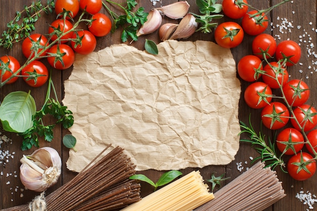 Three types of spaghetti, tomatoes and herbs on wood top view with copy space