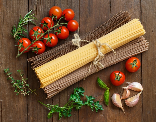 Three types of spaghetti, tomatoes and herbs on wood