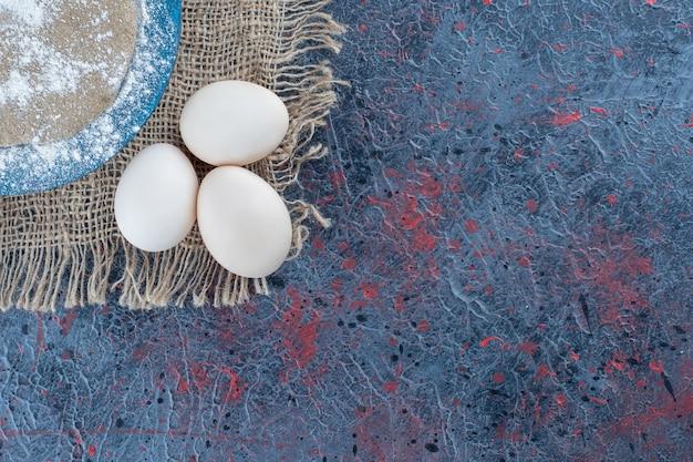Tre uova di gallina fresche crude con pasta su un sacco.
