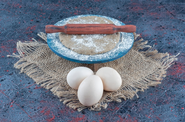 Three uncooked fresh chicken eggs with dough on a sackcloth.