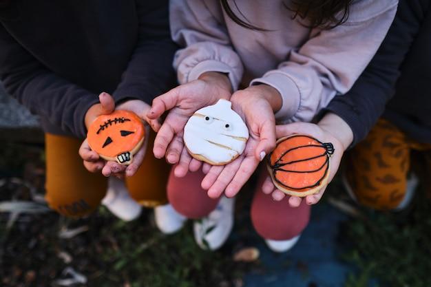 認識できない3人の子供が、手作りのハロウィーンの装飾が施されたクッキーを手に持っています