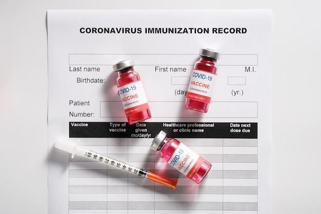 Три стеклянных флакона с вакциной для вакцинации от covid-19 и шприц
