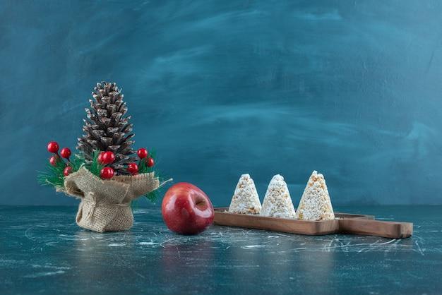 Tre torte ricoperte di vaniglia, una mela e un ornamento natalizio sul blu.