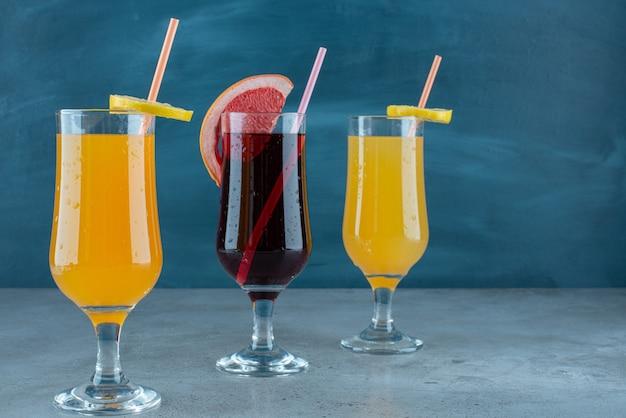 ストローとガラスのカップに3つのさまざまなジュース。
