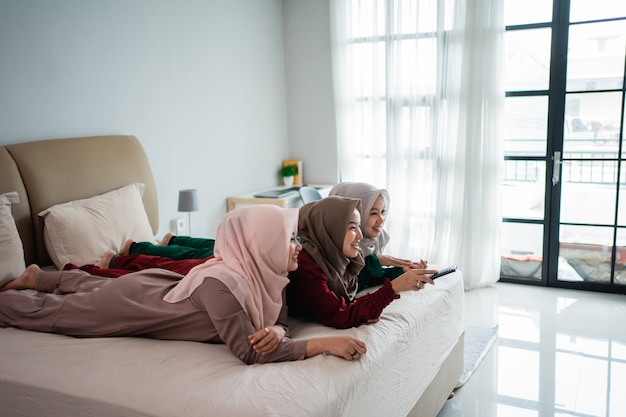 Three veiled woman lying on the bed enjoy watching the tv