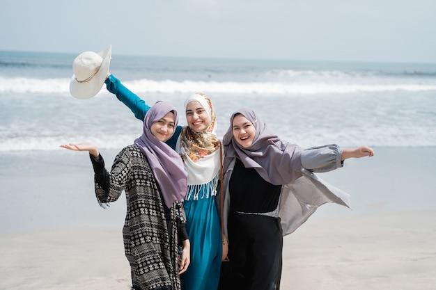 가려진 여성 3 명은 해변에서 휴가를 즐깁니다.