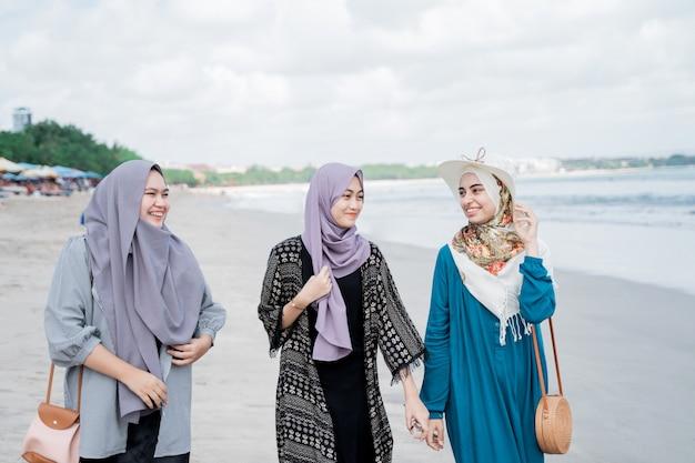 Three veiled women enjoy a holiday on the beach