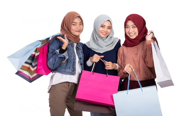 Three veiled women excited when carrying paper bag