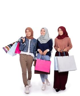 紙袋を運ぶときに興奮している3人のベールに包まれた女性
