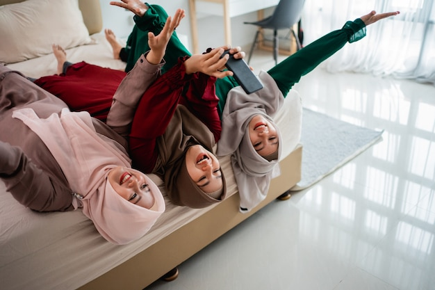 Три прикрытые женщины ложатся и поднимают руки на кровати, принимая селфи вместе