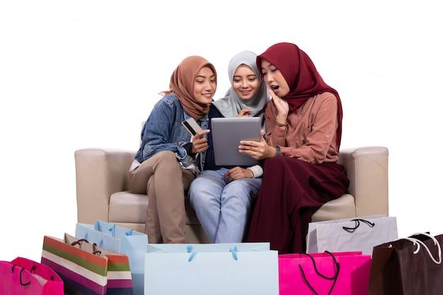 紙袋の近くに座って、オンラインショップで購入するためにクレジットカードを持っている3人のベールに包まれた女性
