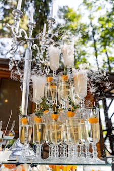 Three vertical raw of full glasses of champagne. candelstick with pearl threads. selective focus.