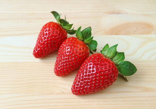 Three vibrant red color fresh ripe strawberry fruits isolated on wooden table
