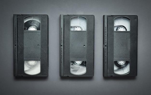 Три видеокассеты на сером фоне. ретро-технологии 80-х годов. вид сверху.