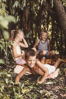 Трое деревенских детей играют в хижине, которую они сами построили из листьев и веток.