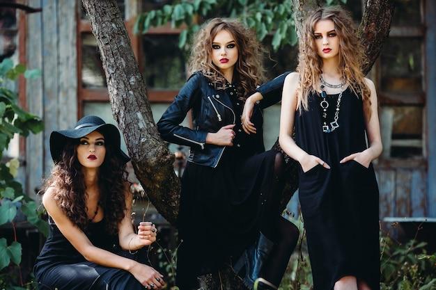 Tre donne vintage come streghe, posano davanti a un edificio abbandonato alla vigilia di halloween