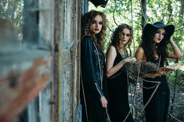 Tre donne vintage come streghe, posano davanti a un edificio abbandonato con libri in mano alla vigilia di halloween