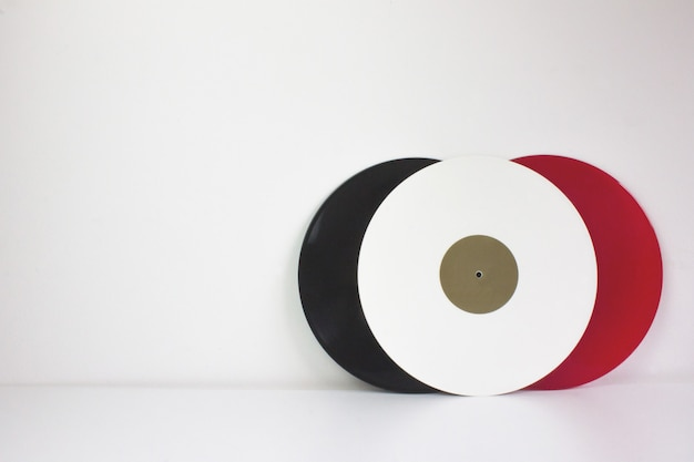 Three vinyls, black, red and white, on white, with white space.