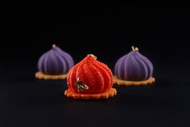 Three violet and orange cakes with matte surface.