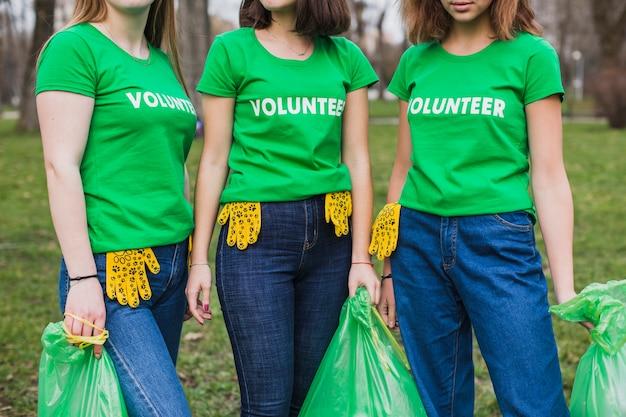 쓰레기 봉투가있는 자원 봉사자 3 명