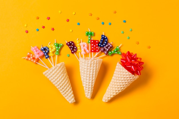 Three waffle cones in the ribbon bow; happy birthday text candles with sprinkles on yellow backdrop