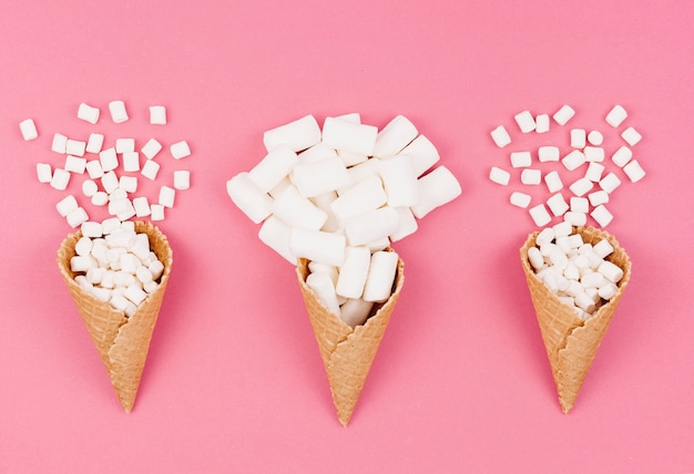 Three waffle cones with marshmallows on table