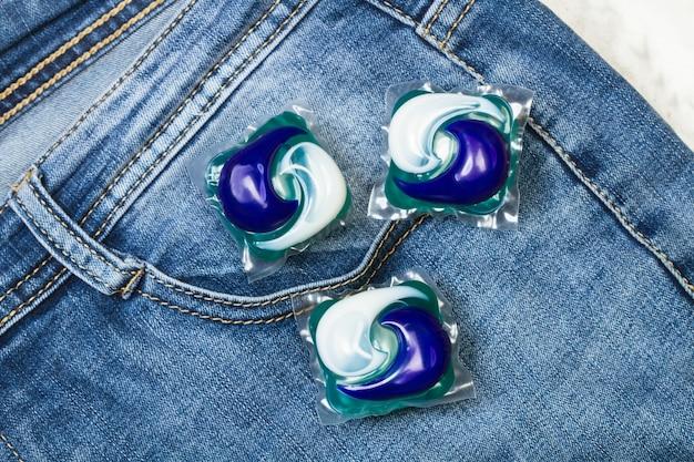 Три капсулы моющего средства для стиральной машины на синих джинсах, вид сверху