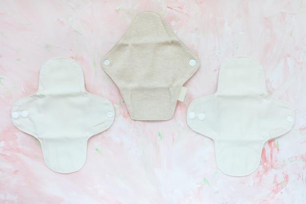 3つの白とベージュの洗える健康的な再利用可能な月経パッド、ピンクの壁に衛生綿、コピースペース。フェミニンな抗アレルギー衛生、環境にやさしい、プラスチックを含まない、グリーンライフスタイルのコンセプト