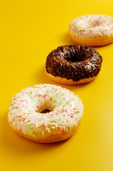 Three white and black donuts on yellow wall