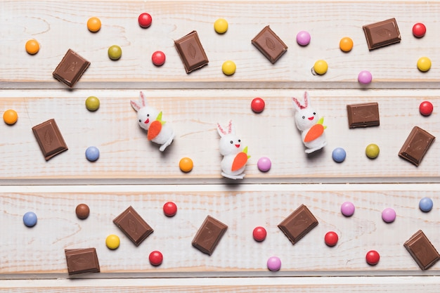 Three white bunnies surrounded with multicolored gems and chocolate pieces over desk