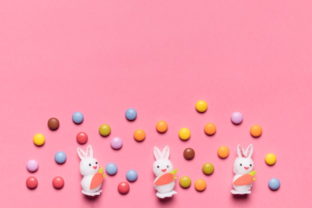 Three white bunnies with colorful gem candies on pink background