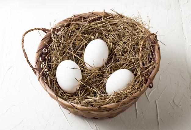 白い背景の上の干し草の巣の3つの白い鶏の卵。
