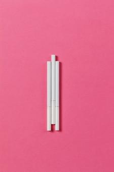 ピンクのバラの背景に3つの白いタバコ