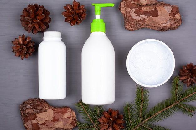 Three white container with body care cosmetics on a gray background in the forest theme top view