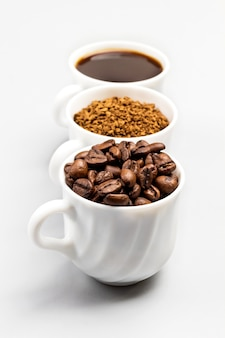 Three white cups with coffee beans, ground coffee and coffee drink isolated on white background
