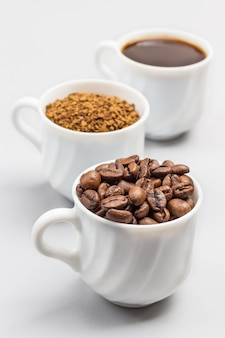 Three white cups with coffee beans, ground coffee and coffee drink. white background. close up