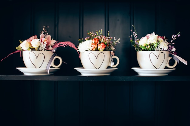 Three white cups with flowers on the shelf.