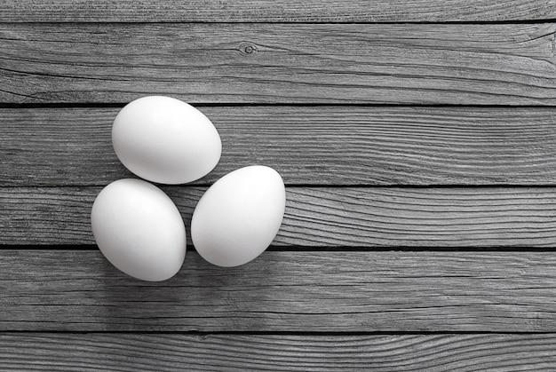 Три белых яйца на сером дереве