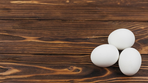 Three white eggs on wooden table