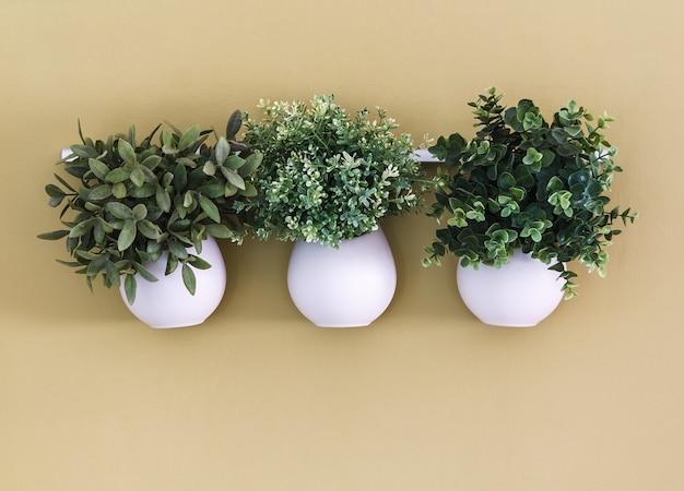 Три белых цветочных горшка с цветами, висящими на стене