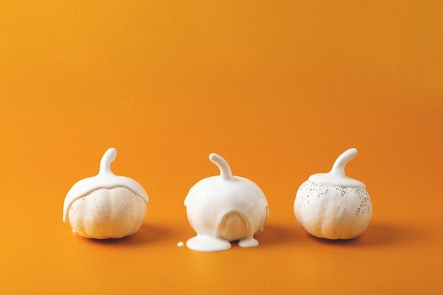 Три белых хэллоуина тыквы с жидкой краской течет минимальный праздничный сезон концепции фон