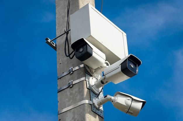Three white outdoor cctv cameras on the concrete pillar on the street