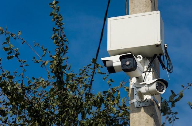 通りのコンクリート柱に3つの白い屋外cctvカメラ