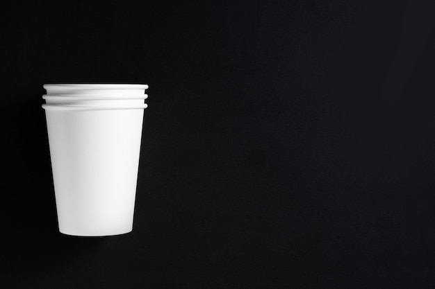 黒の背景にコーヒーの3つの白い紙コップ。テキストの場所。上面図。