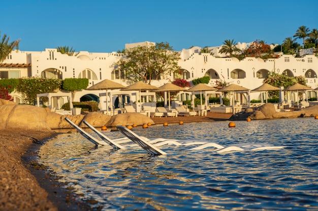 이집트 샤름 엘 셰이크(sharm el sheikh)의 아침 일출 동안 열대 해변의 바닷물에 3개의 흰색 플라스틱 일광욕용 라운저가 있습니다. 여행과 자연 개념