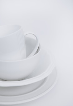 Three white plates and a cup on a white background