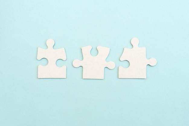 青い背景の上の3つの白いパズルのピース